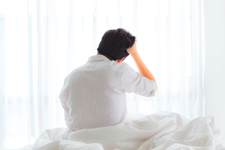 Black hair of young business asian man sitting near the big white window while using hand slick his hair on bed after waking up with sunrise at morning, back view.
