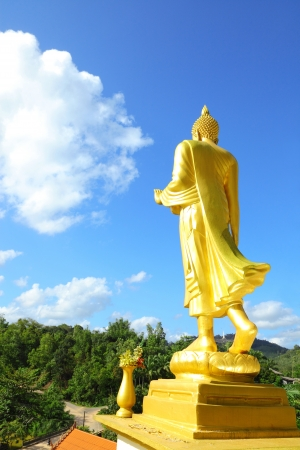 Gold Buddha give murcy on the high mountain with blue sky background photo