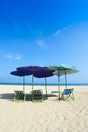 umbella: Comfort chairs and umbrella on the beach under the blue sky for background