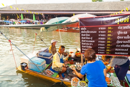 SUMUTHSONGKRAM,THAILAND-DECEMBER 30:The merchants sell the foods at Umpawa Floating Market where the most popular floating market in Thailand at Umpawa on December 30,2012 in Samuthsongkram,Thailand