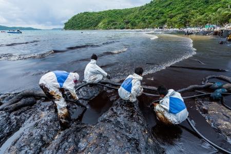 oil spill: Rayong, Tailandia, 31 lug Molti lavoratori che utilizzano la macchina aspirare ad aspirare il greggio sulla spiaggia di Ao Prao su incidente fuoriuscita di petrolio da PTT Ao Prao Beach a isola Samet luglio 31,2013 a Rayong, Tailandia