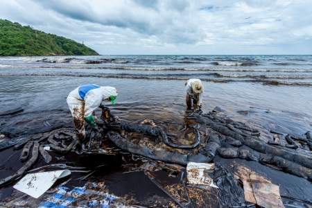 RAYONG,THAILAND-July 31  Workers use the plastic bags to keep the crude oil on oil spill accident on Ao Prao Beach at Samet island on July 31,2013 in Rayong,Thailand