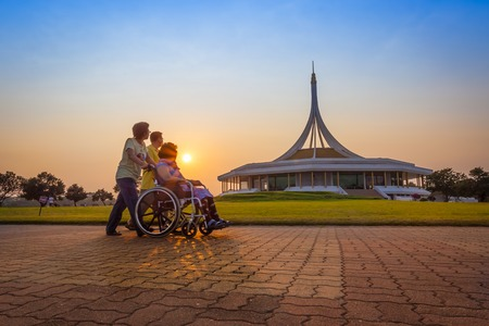 BANGKOK,THAIL AND-FEBRUARY 19  Son and daughter take her mother on wheel chair for exercise and walking for relax with warm light at Suanluang R  9 garden on February 19,2014 in Bangkok,Thailand