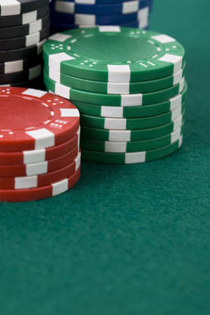 Closeup of poker chips in stacks on green felt card table surface photo