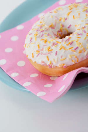 serviette: Closeup of donut with icing and colored sprinkles on spotty pink serviette on plate on light background Stockfoto