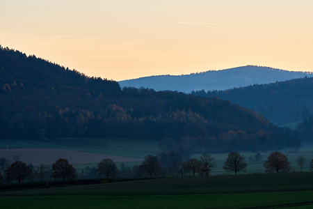 Sunset over hills with forrests and fields Standard-Bild