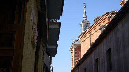 Church tower overlooks dark alley in Madrid