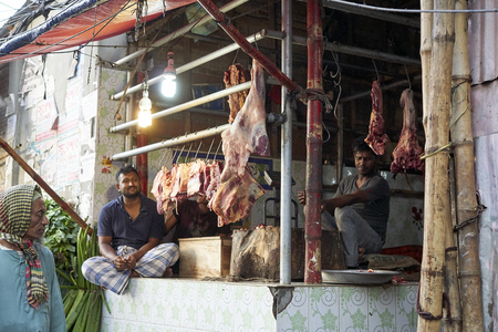 DHAKA, BANDLADESH - 5. APRIL 2017: Two men working at a butchery presenting the meat openly without cooling Publikacyjne