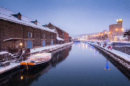 selective focus at location of Otaru Canal in Winter Evening, movement of people are walking alongside canal, Hokkaido, Japan