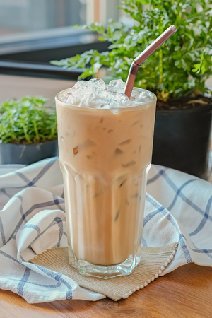 fredo: Iced Coffee  with Dark brown straw on decorative background