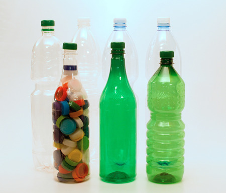 greeen: White and greeen plastic bottles with caps for recycling