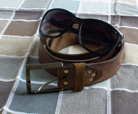 leather belt: Leather belt, glasses on checkered fabric background Stock Photo