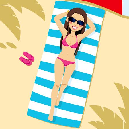흰색과 파란색 줄무늬 수건에 해변에 누워 분홍색 비키니를 입고 아름 다운 갈색 머리 여자