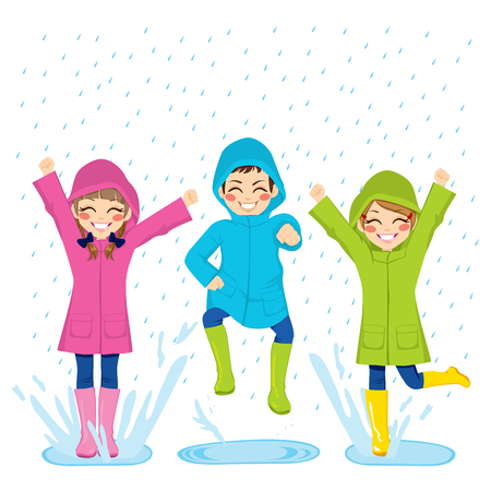 Little kids playing on puddles wearing colorful raincoats and boots