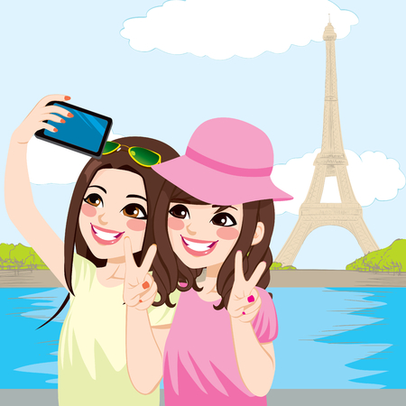 Beautiful young Japanese girl friends taking selfie photo together in front of Eiffel Tower in Paris with mobile phone camera