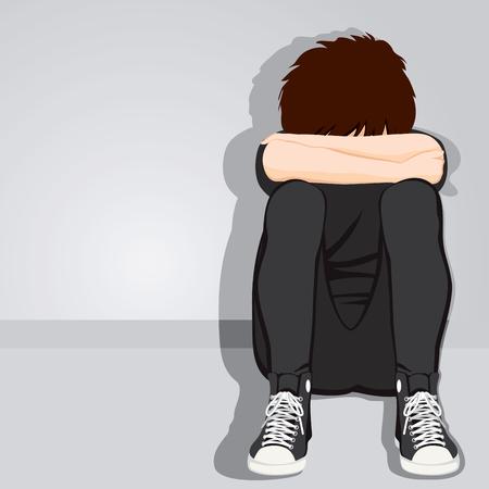 Sad muchacho adolescente desesperado ocultando su rostro sentado en el suelo en el fondo gris con ropa oscura