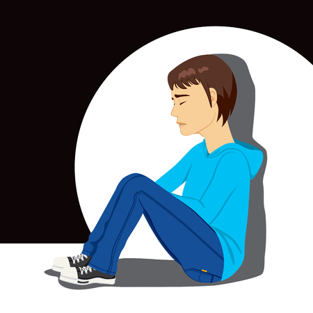 Sad teenager boy crying sitting on floor under white spot light on dark background Vector