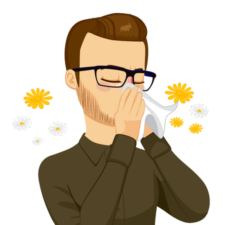 Young brown haired man sneezing blowing nose on white tissue because of spring allergy