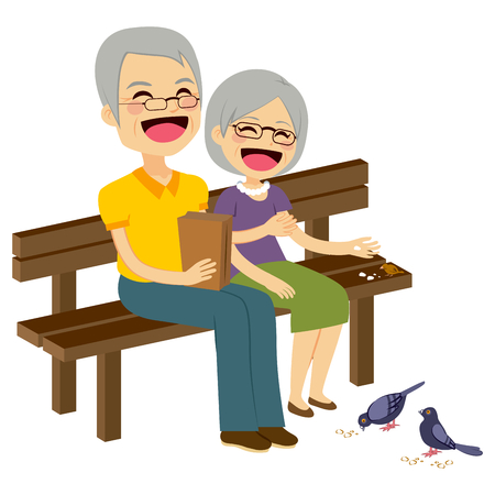 happy couple: Cute senior couple feeding birds with breadcrumbs sitting on bench