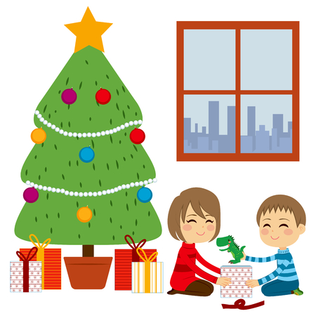 Two cute happy siblings children opening gifts together from Christmas Tree