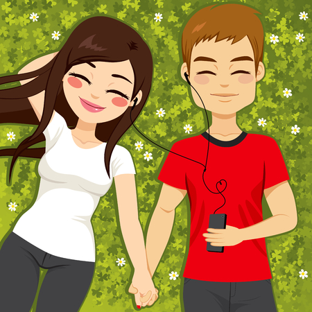 hand holding flower: Cute young couple relaxed listening to music lying on clover grass field