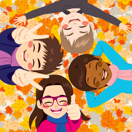 lying on leaves: Happy friends lying on colorful autumn leaves