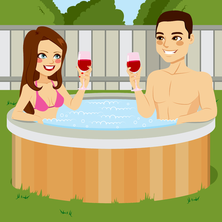 toasting: Young couple enjoying outdoor hot tub toasting with red wine