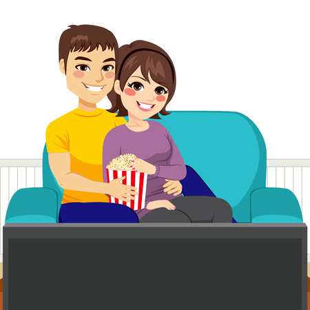 woman watching tv: Cute young couple watching movie together on couch and eating popcorn