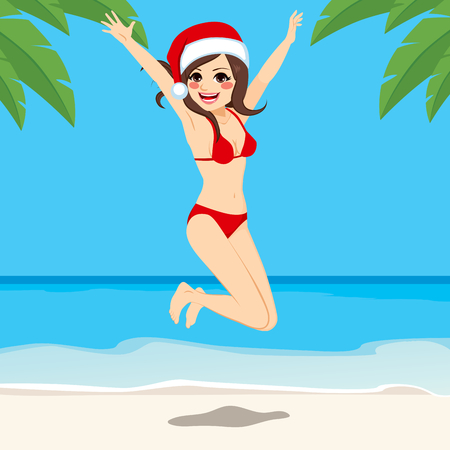 woman arms up: Beautiful young brunette girl wearing Santa hat jumping on Christmas vacation at beach