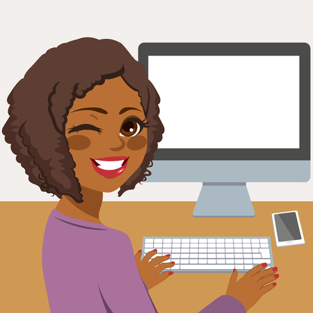 Happy young African American woman using desktop computer