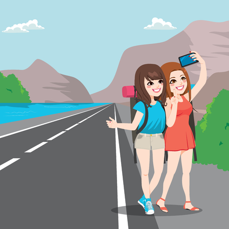 girl pose: Two young girl friends on travel making selfie with hitchhiking pose on roadside