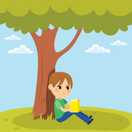 Young little kid reading a book sitting under tree