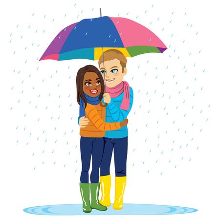 Young interracial couple embracing under rain holding rainbow umbrella romantic mood