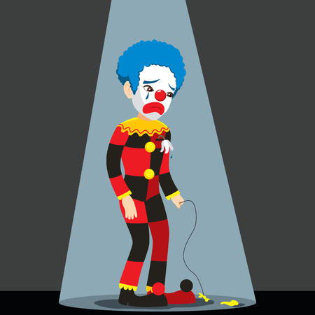Sad clown standing under spotlight with punctured balloon crying