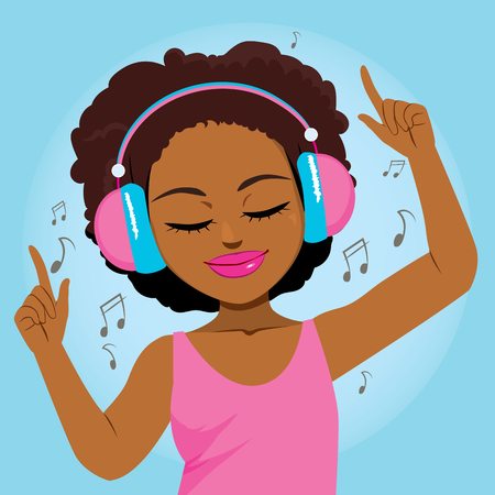 Beautiful young black woman enjoying music with headphones and dancing