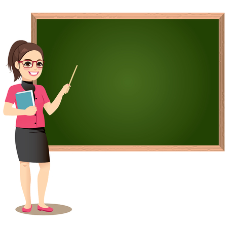 Female teacher in classroom teaching lesson pointing at greenboard and holding book