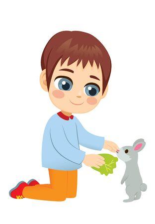 Young little boy feeding cute pet rabbit