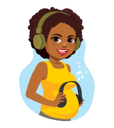 Beautiful black pregnant woman holding headphones on her belly while enjoying music