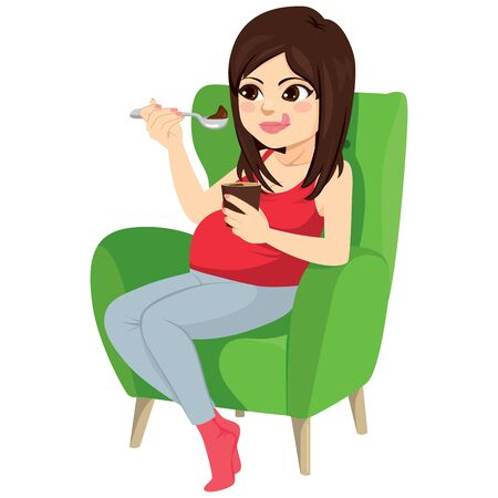 Beautiful brunette pregnant woman holding spoon eating chocolate ice cream sitting on green armchair craving concept
