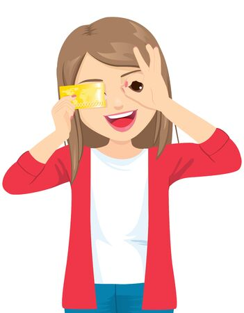 Young beautiful happy woman holding credit card smiling doing ok sign with hand on eye looking through fingers