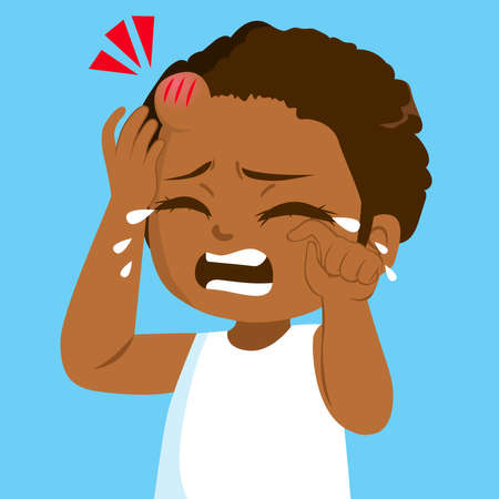 Sad little black girl crying in pain with bump bruise on forehead