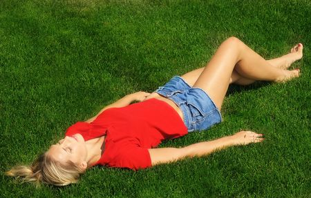 a bathing place: young woman is sunbathing in the park