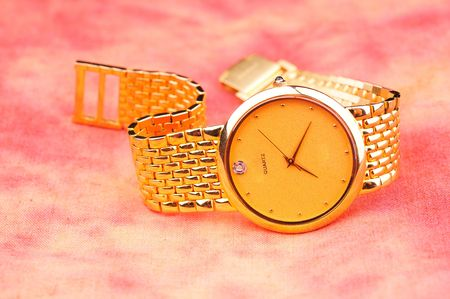 watch over: golden watch over red background