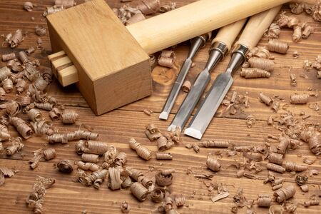 Chisel and wooden mallet with wood shavings. Carpenter cabinet maker hand tools on the workbench.