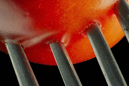 Fork with cherry tomato close-up. Isolated image on a black background. Macro photo. Stock Photo