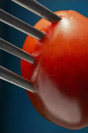 Photo of a fork with cherry tomato close-up Stock Photo