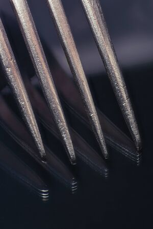 Close-up of a fork with reflection on black glass.