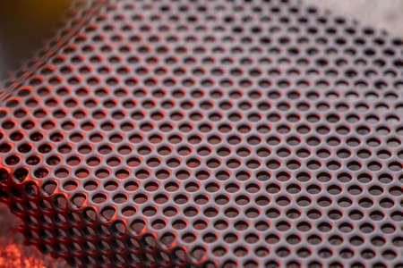 Black ventilation holes of a metal computer case. Aluminum grill close-up.