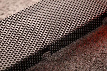 Black ventilation holes of a metal computer case. Aluminum grill close-up. Banco de Imagens