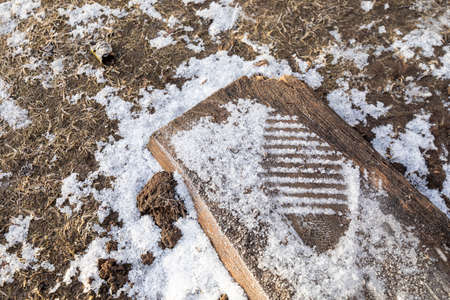 Footprint from the sole of a shoe in the snow. Remains of snow after winter. Standard-Bild